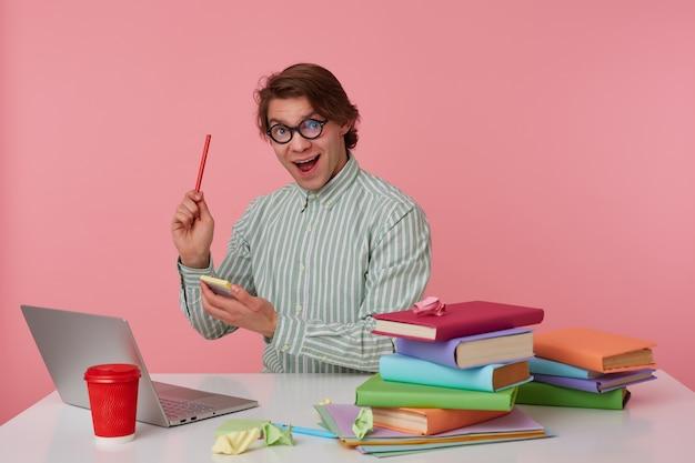 Młody facet w okularach siedzi przy stole i pracuje z laptopem, patrzy w kamerę, trzyma w ręku ołówek i naklejki, ma świetny pomysł, odizolowany na różowym tle.