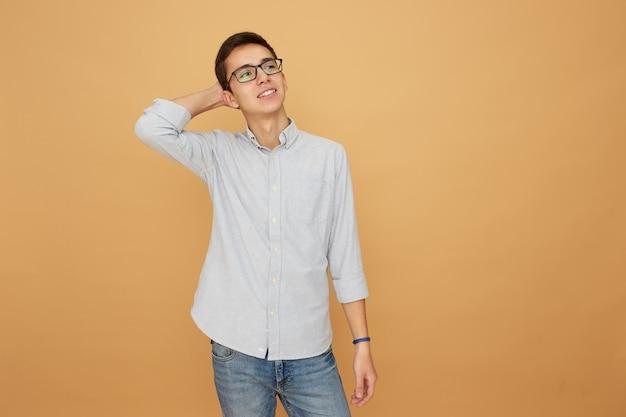 Młody facet w okularach, ubrany w jasnoniebieską koszulę i dżinsy stoi z ręką na głowie na beżowym tle w studio.