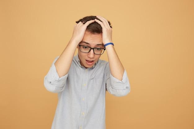 Młody facet w okularach, ubrany w jasnoniebieską koszulę i dżinsy stoi z rękami na głowie na beżowym tle w studio.