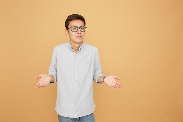 Młody facet w okularach, ubrany w jasnoniebieską koszulę i dżinsy stoi z rozłożonymi rękami na beżowym tle w studio.