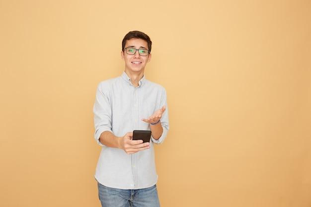 Młody facet w okularach ubrany w jasnoniebieską koszulę i dżinsy trzyma w ręku telefon komórkowy na beżowym tle w studio .