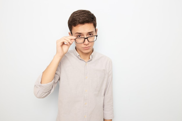 Młody facet w okularach ubrany w lekką koszulę stoi z ręką na okularach na białym tle w studio.