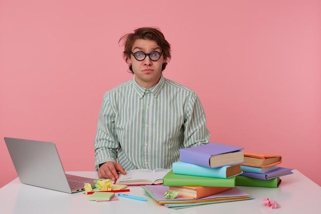 Młody facet w okularach, ubrany w pustą koszulę, siedzi przy stole z książkami, pracuje przy laptopie, wygląda na zszokowanego i zdezorientowanego. pojedynczo na różowym tle.