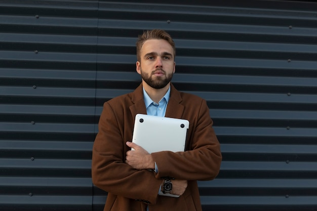 Młody facet w płaszczu iz laptopem pozuje przy metalowej ścianie