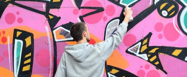 Młody facet w szarej bluzie z kapturem maluje graffiti w kolorze różowym i zielonym