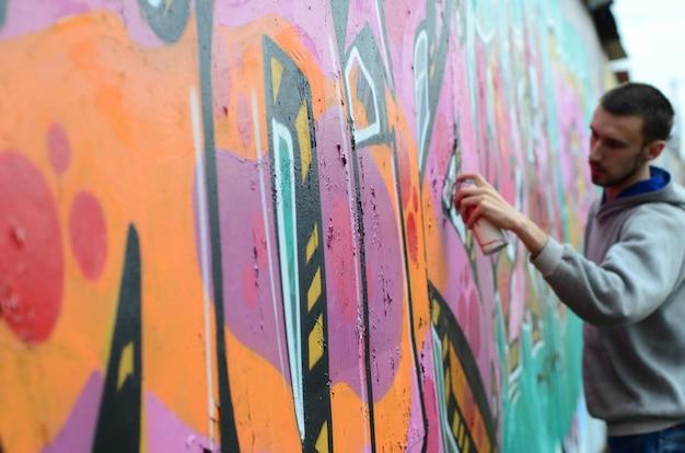 Młody facet w szarej bluzie z kapturem maluje graffiti