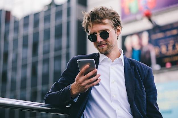 Młody facet z blond włosami w okularach przeciwsłonecznych patrzy na swój telefon komórkowy będąc na zewnątrz w letni dzień