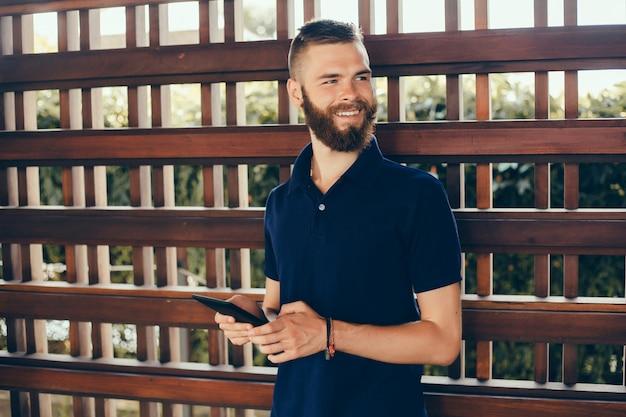 Młody facet z brodą pracuje w kawiarni, freelancer używa tabletu, wykonuje projekt