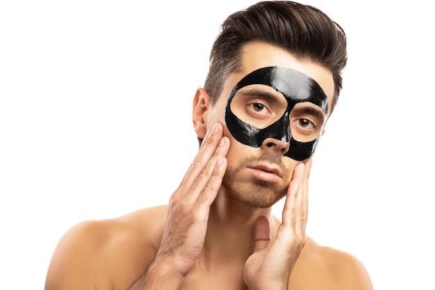Młody facet z czarną maską węglową na jego twarzy na bielu.