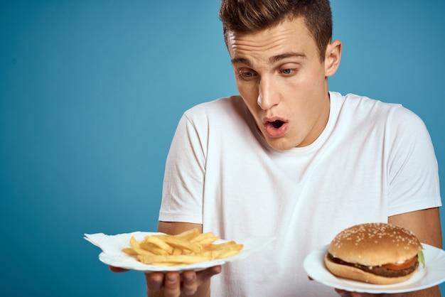 Młody facet z frytkami i hamburgerem