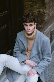 Młody facet z płaszczem siedzi średni strzał