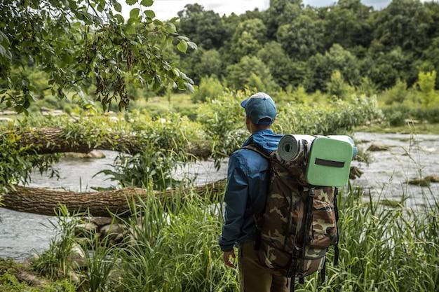 Młody facet z plecakiem turystycznym przekraczającym jeziora
