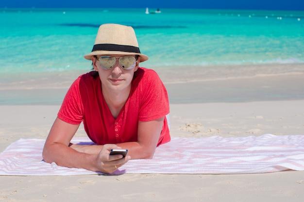 Młody facet z telefonem komórkowym na tropikalnej biel plaży