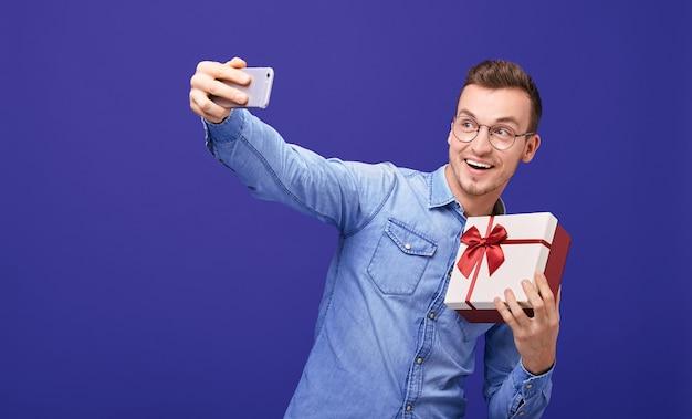 Młody facet z teraźniejszością w jego ręce robi selfie.