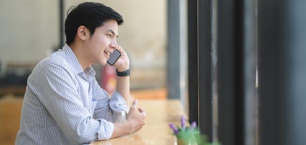 Młody fachowy biznesmena mówienie na telefonie z jego klientem w nowożytnym biurze