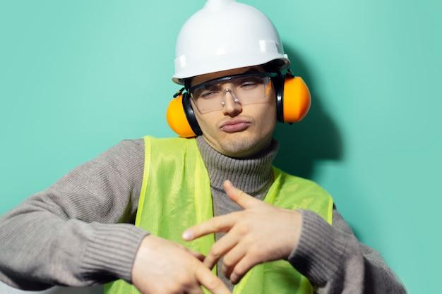 Młody, fajny budowniczy, tańczący inżynier, noszący słuchawki ochronne, kask, gogle i kamizelkę odblaskową na ścianie w kolorze aqua menthe.