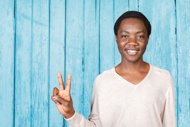 Młody fajny czarny człowiek znak zwycięstwa
