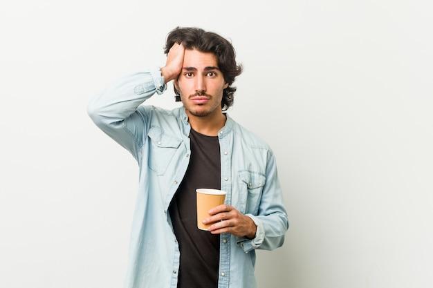 Młody fajny człowiek pije kawę jest zszokowany