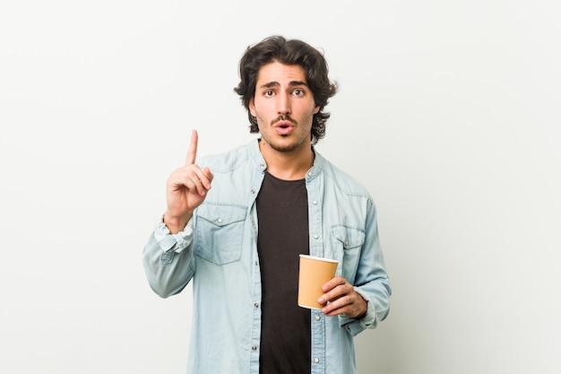 Młody fajny człowiek pije kawę mając świetny pomysł