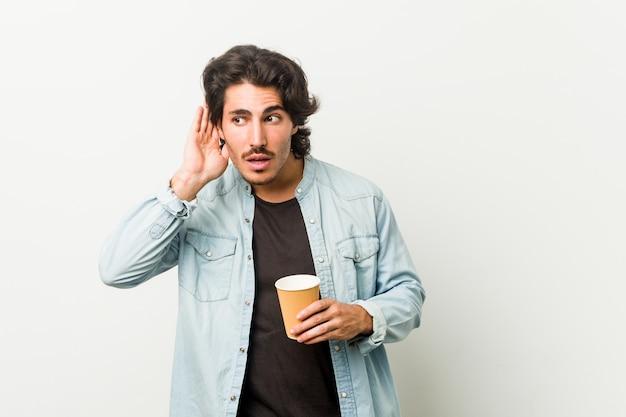 Młody fajny człowiek pije kawę, próbując słuchać plotek.