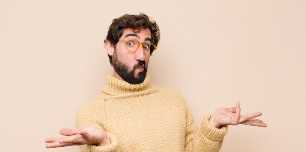 Młody fajny mężczyzna czuje się zdziwiony i zdezorientowany, wątpi, waży lub wybiera różne opcje z zabawnym wyrazem twarzy na płaskiej ścianie