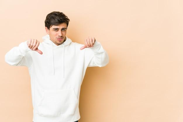 Młody fajny mężczyzna pokazuje niechęć gest, kciuki w dół