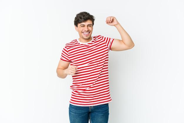 Młody fajny mężczyzna świętuje wyjątkowy dzień, skacze i energicznie podnosi ramiona.