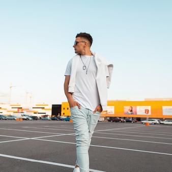 Młody fajny mężczyzna w modnych białych ubraniach w stylowych czarnych okularach przeciwsłonecznych z modną fryzurą spaceruje w jasny słoneczny dzień na miejskim parkingu. model przystojny amerykański facet. letni styl.