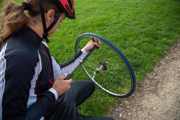 Młody fajny rowerzysta mężczyzna w odzieży sportowej i kask ochronny naprawy komory powietrznej roweru koło w parku
