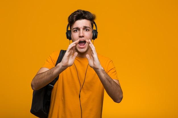 Młody fajny studencki mężczyzna słucha muzyka z hełmofonami ono uśmiecha się wesoło wskazuje z palcem wskazującym daleko od.