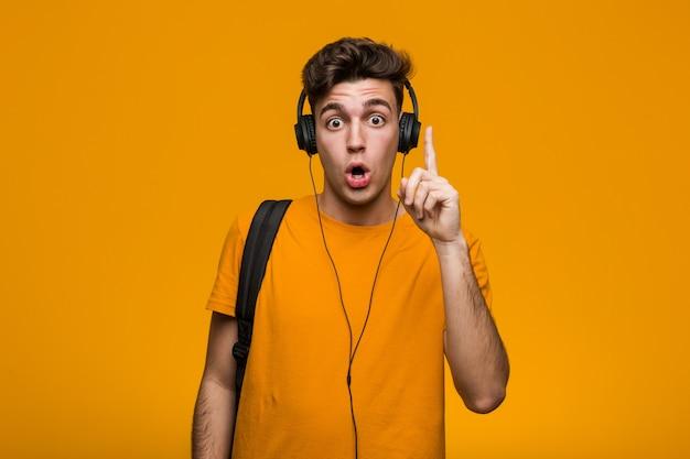 Młody fajny studencki mężczyzna słucha muzyka z hełmofonami relaksował myśleć o coś patrzeje odbitkową przestrzeń.