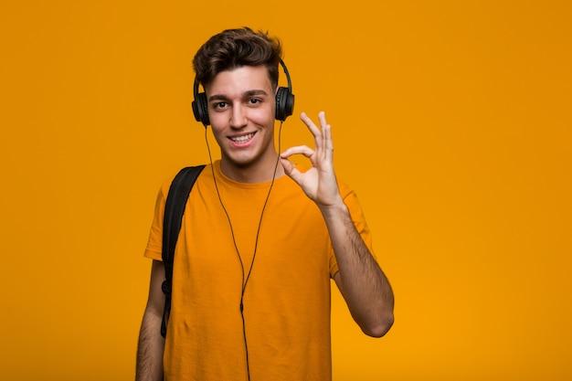 Młody fajny student człowiek słuchania muzyki w słuchawkach zaskoczony, wskazując na siebie, uśmiechając się szeroko.