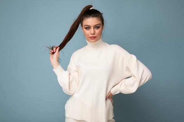 Młody fascynujący kaukaski moda brunetka kobieta ubrana w biały sweter na białym tle na niebieskim tle ściany. skopiuj miejsce