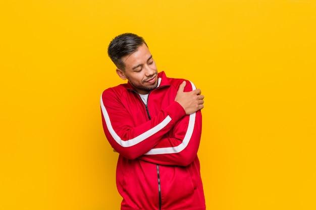 Młody filipiński fitness mężczyzna przytula, uśmiechając się beztrosko i szczęśliwy.