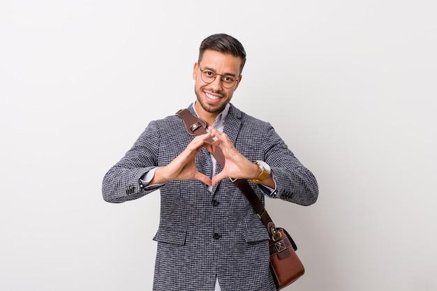 Młody filipiński mężczyzna biznesu na białej ścianie, uśmiechając się i pokazując kształt serca rękami.