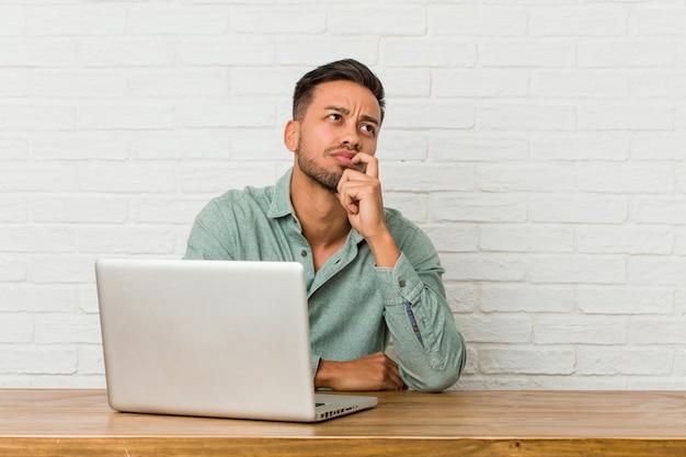 Młody filipiński mężczyzna siedzący działanie z jego laptopem relaksował główkowanie o coś patrzeje odbitkową przestrzeń.