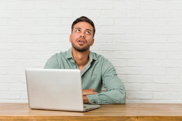 Młody filipiński mężczyzna siedzący z laptopem zmęczony powtarzającymi się zadaniami.