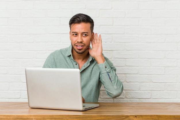 Młody filipiński mężczyzna siedzi pracując z laptopem, próbując słuchać plotek.