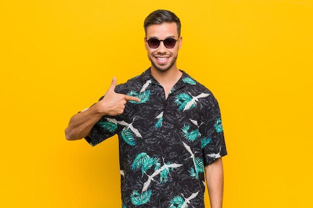 Młody filipiński mężczyzna ubrany w letnie ubrania osoba wskazująca ręką na przestrzeni kopii koszuli, dumny i pewny siebie