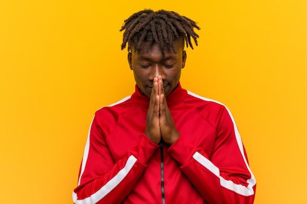 Młody fitness afrykański mężczyzna, trzymając się za ręce w modlić się w pobliżu usta, czuje się pewnie.