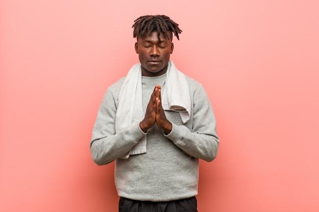 Młody fitness afrykański murzyn, trzymając się za ręce w modlić się w pobliżu ust, czuje się pewnie.