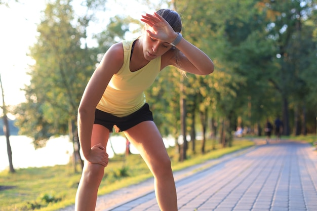 Młody fitness atrakcyjny sportowy dziewczyna odpoczynek po intensywnym wieczornym biegu na świeżym powietrzu o zachodzie słońca w parku.