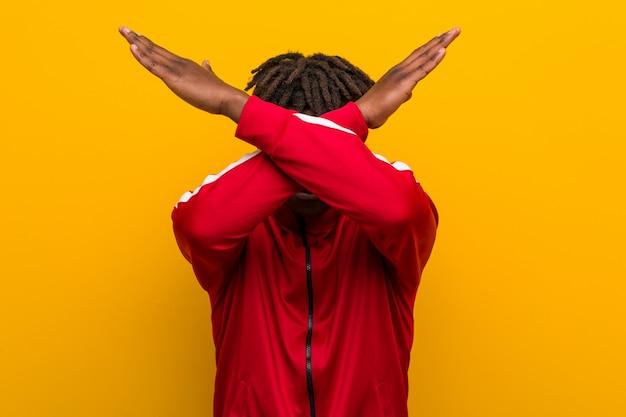 Młody fitness czarny człowiek trzyma dwa ramiona skrzyżowane, pojęcie negacji.
