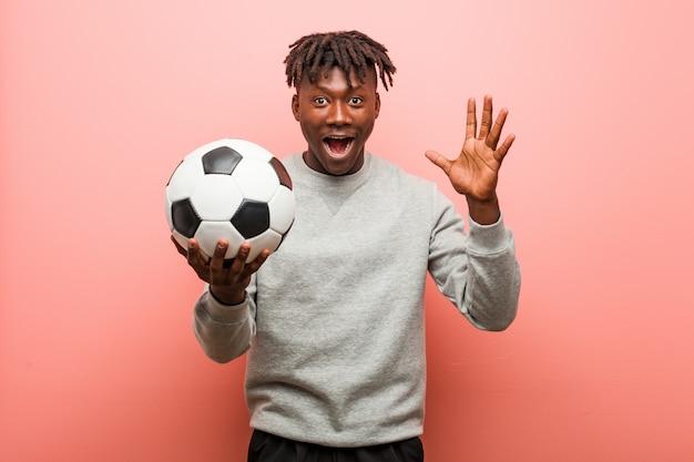 Młody fitness czarny człowiek trzyma piłkę świętuje zwycięstwo lub sukces