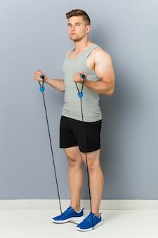 Młody fitness kaukaski mężczyzna ćwiczy z gumką.