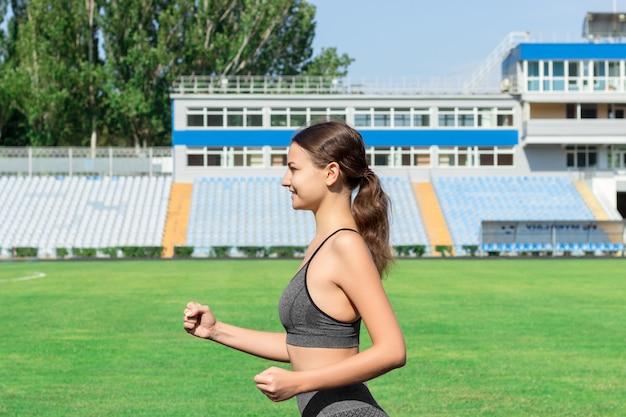 Młody fitness kobieta biegacz działa na torze stadionu. trening w godzinach porannych. ludzie sportu i fitness koncepcja