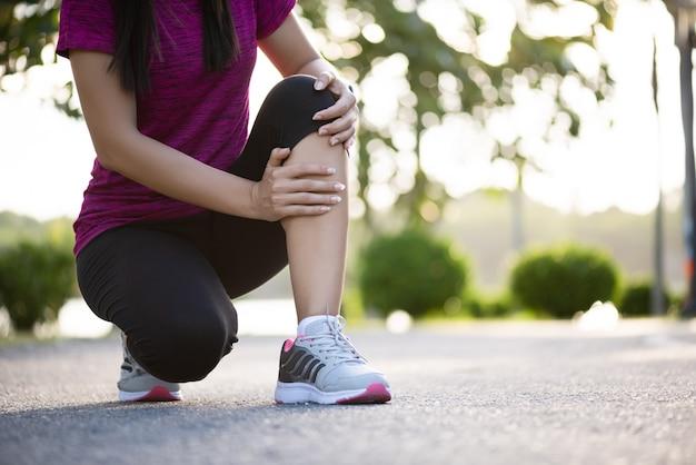 Młody fitness kobieta biegacz poczuć ból na kolanie w parku