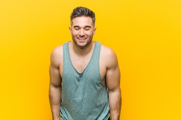Młody fitness mężczyzna na żółtym tle śmieje się i zamyka oczy, czuje się zrelaksowany i szczęśliwy.
