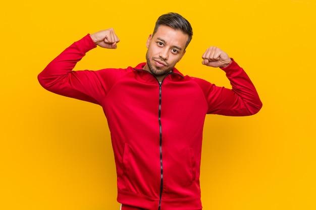 Młody fitness mężczyzna pokazuje siłę gest z rękami, symbol kobiecej siły