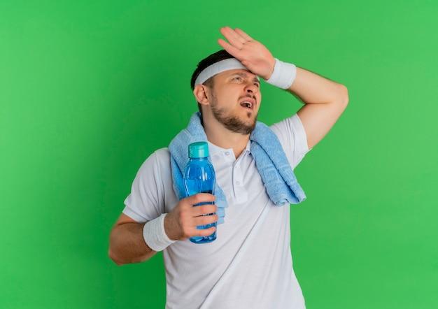 Młody fitness mężczyzna w białej koszuli z opaską i ręcznikiem na szyi, trzymając butelkę wody zmęczony i wyczerpany po treningu, stojąc na zielonym tle